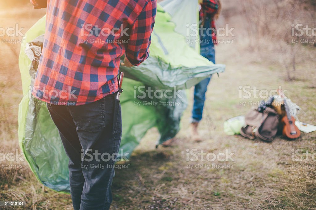 Young couple setting up tent in nature stock photo