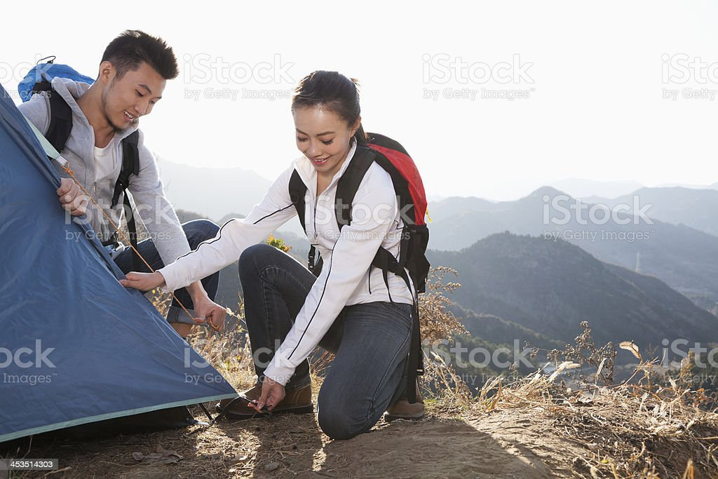 Young couple setting up the tent stock photo