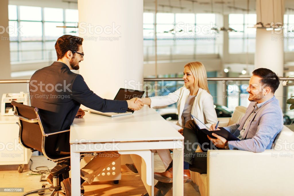 Young couple shaking hands after a successful contract signing stock photo