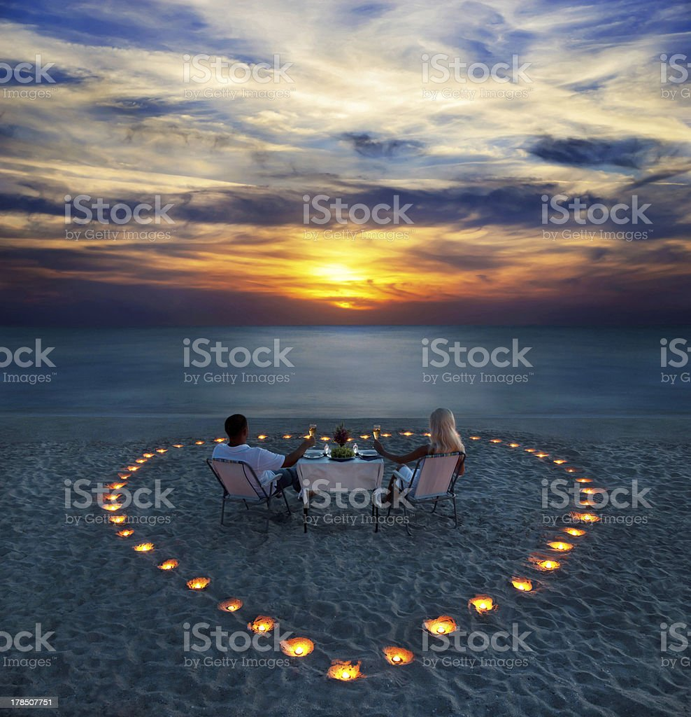 young couple share a romantic dinner on the beach stock photo