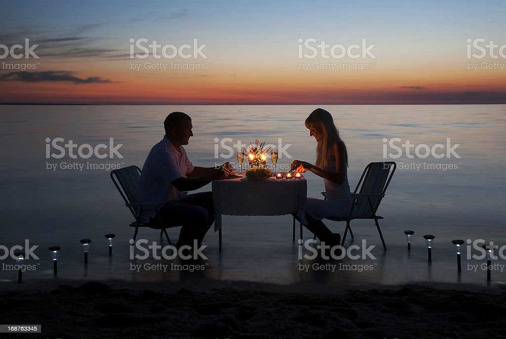 young couple share a romantic dinner with candles on beach stock photo
