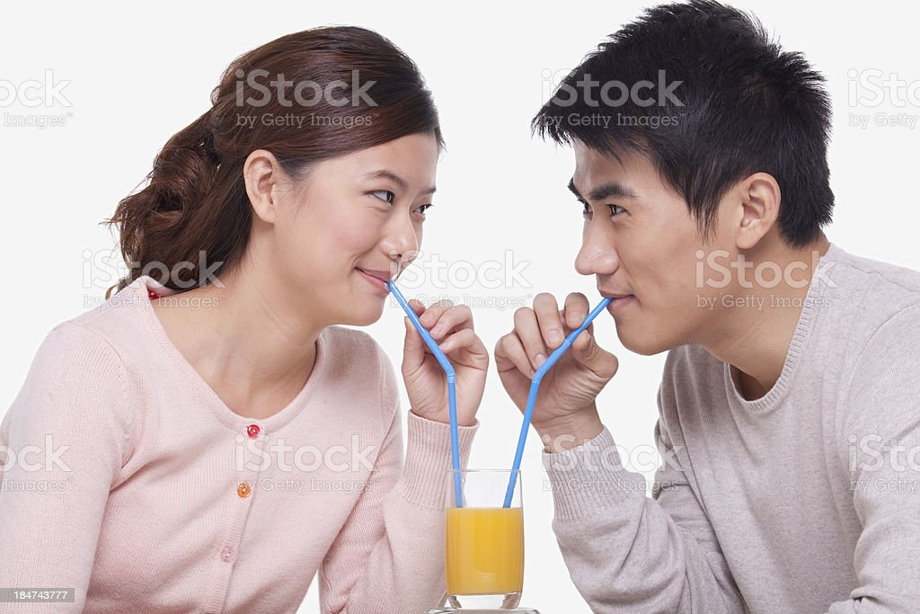 Young couple sharing a glass of orange juice, studio shot royalty-free stock photo
