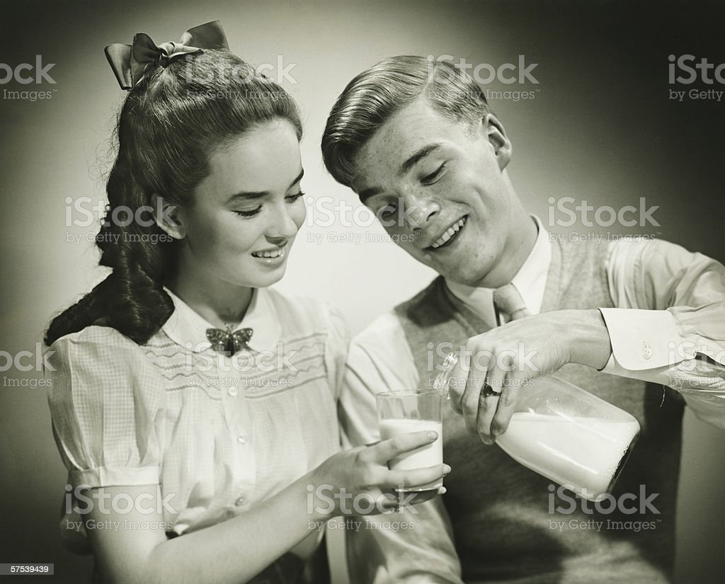 Young couple sharing bottle of milk, smiling, (B&W), close-up stock photo