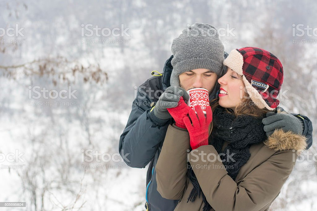 young couple sharing tea outdoors in winter stock photo
