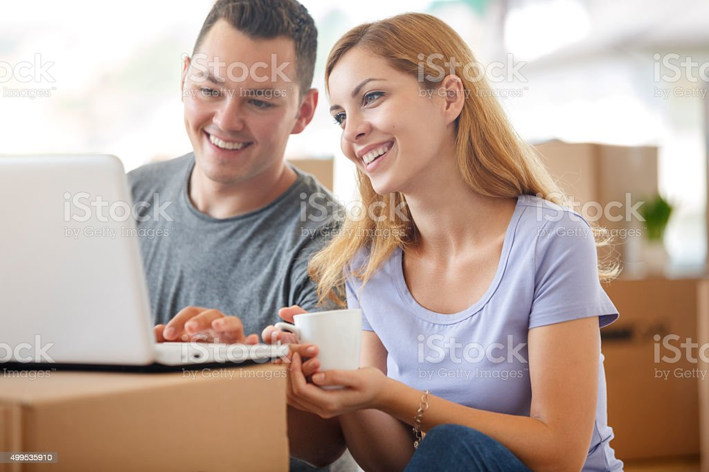 Young couple shopping online for their new home stock photo