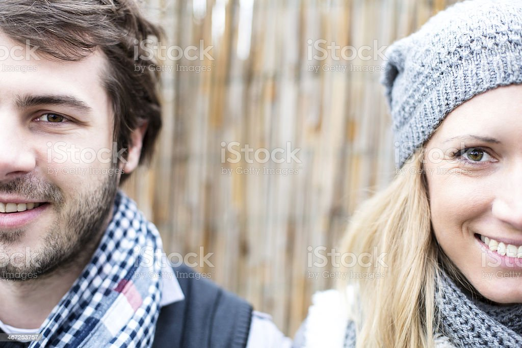 Young couple showing half of each face smiling  royalty-free stock photo
