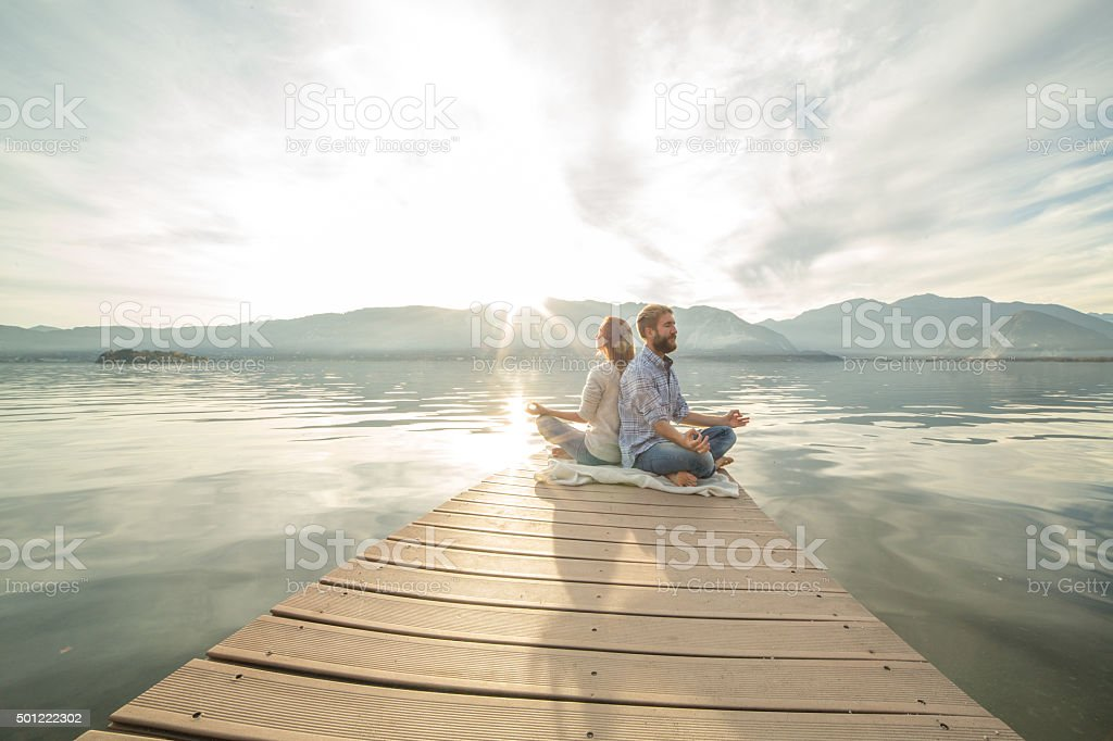 Young couple sits on jetty above lake, exercises yoga stock photo