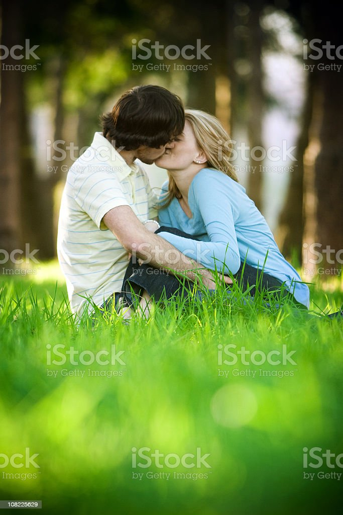 Young Couple Sitting and Kissing in the Grass royalty-free stock photo