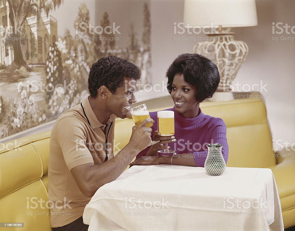 Young couple sitting at table holding glass of beer, smiling royalty-free stock photo