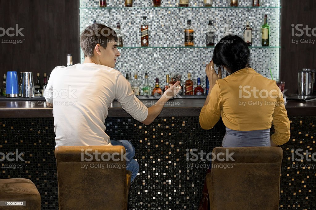 Young couple sitting drinking at the bar stock photo