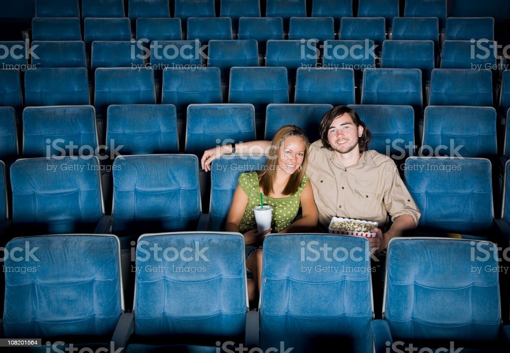 Young Couple Sitting in an Empty Movie Theater royalty-free stock photo