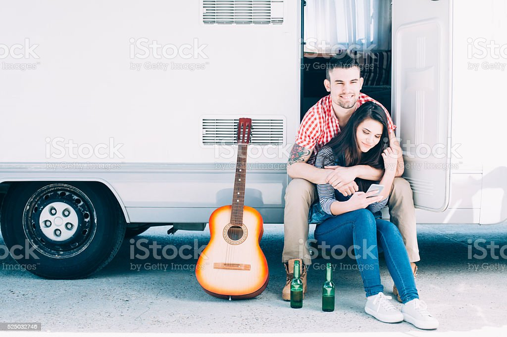 Young couple sitting in front of a camper van stock photo