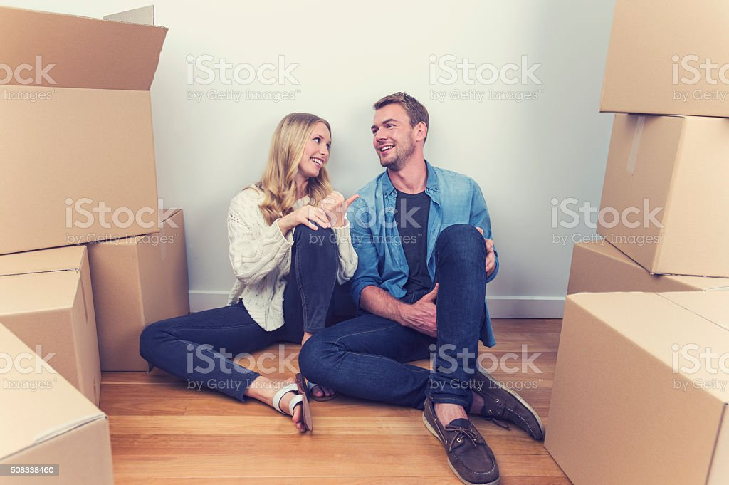 Young couple sitting in new house with packing boxes. stock photo
