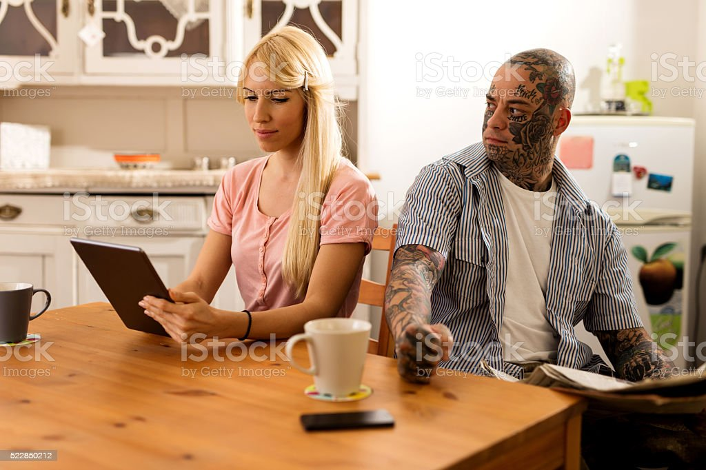 Young couple sitting in the kitchen. stock photo