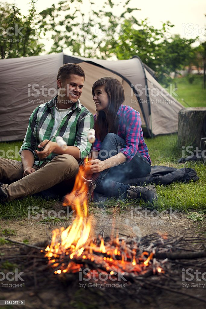 Young couple sitting near a campfire and toasting marshmallow stock photo