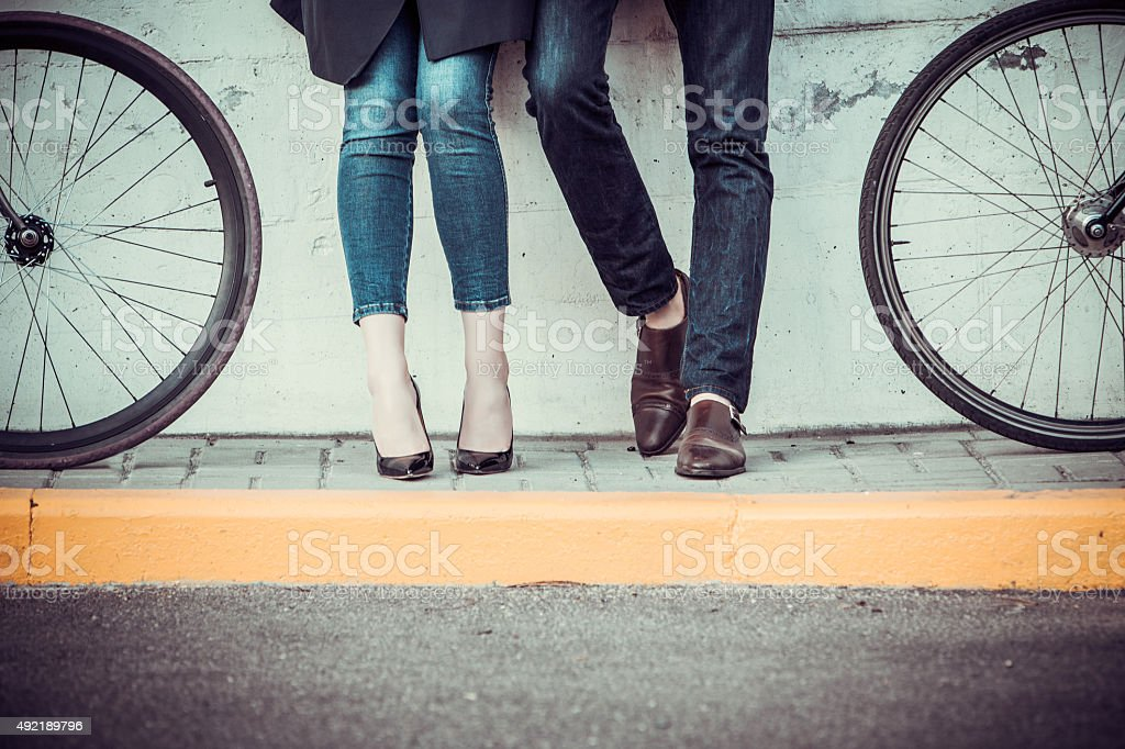 Young couple sitting on a bicycle opposite the city stock photo