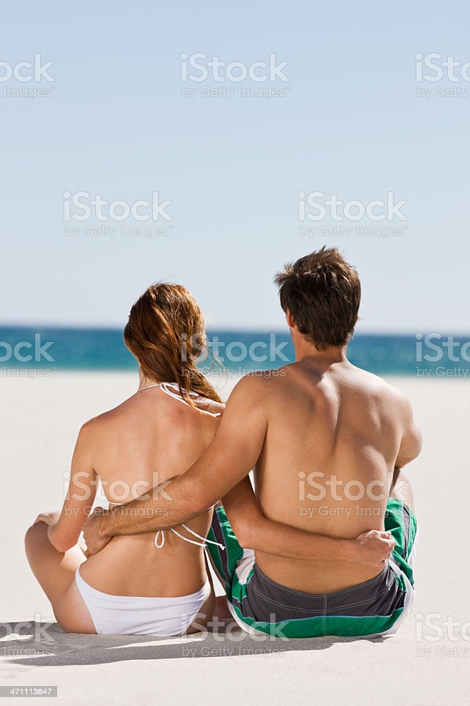 Young couple sitting on beach royalty-free stock photo