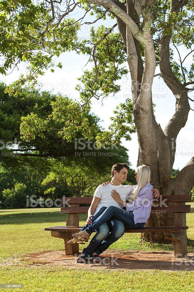 Jeune couple assis sur un banc dans le parc. photo libre de droits