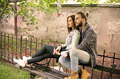 Young couple sitting on bench.