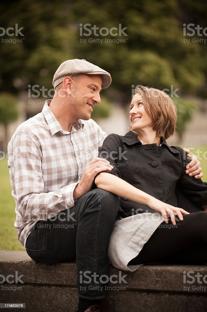 young couple sitting on concrete wall in park royalty-free stock photo