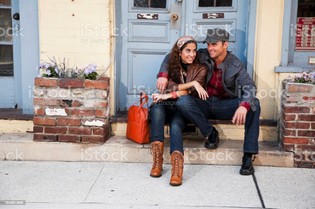 Young couple sitting on doorstep outside shop royalty-free stock photo