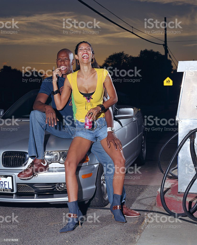 Young couple sitting on hood of car, man biting woman stock photo