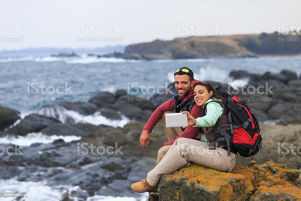 Young couple sitting on rock with digital tablet stock photo