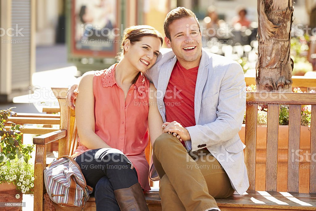 Young Couple Sitting On Seat In Mall Together royalty-free stock photo