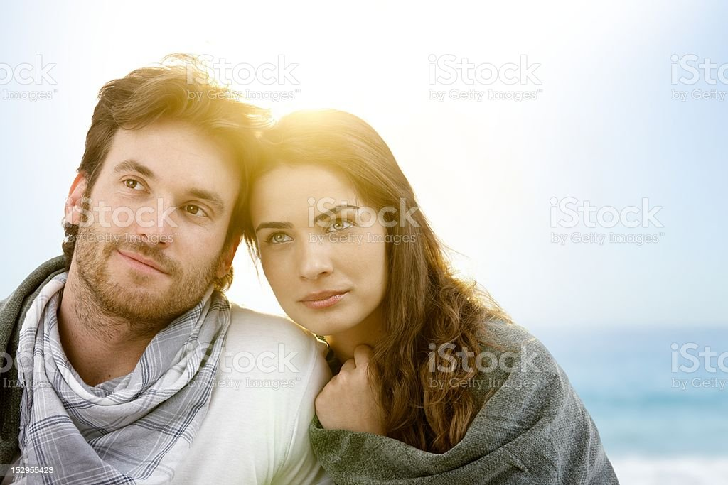 Young couple sitting on summer beach with blanket royalty-free stock photo