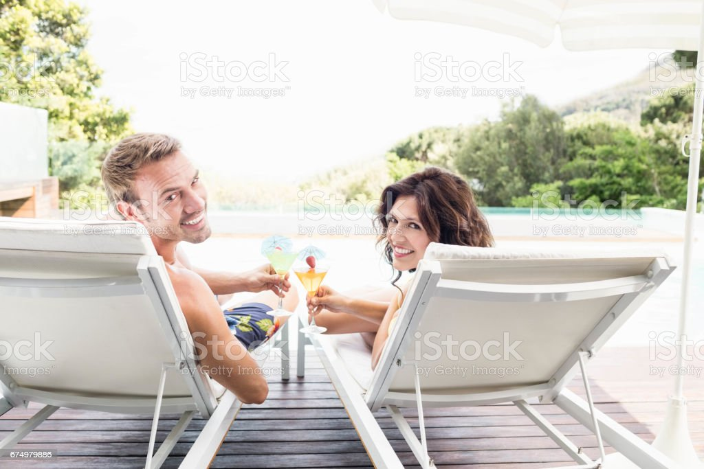 Young couple sitting on sun loungers stock photo