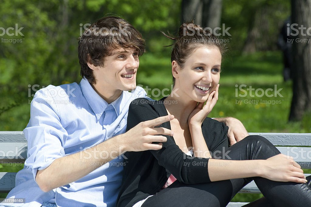 Young couple sitting on the bench in park royalty-free stock photo