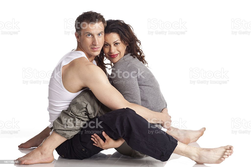 Young couple sitting on the floor and hugging isolated white. royalty-free stock photo