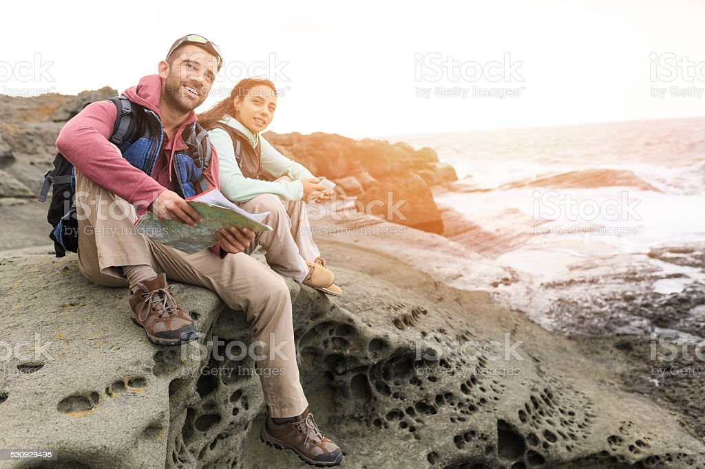 Young couple sitting on top of rocks stock photo