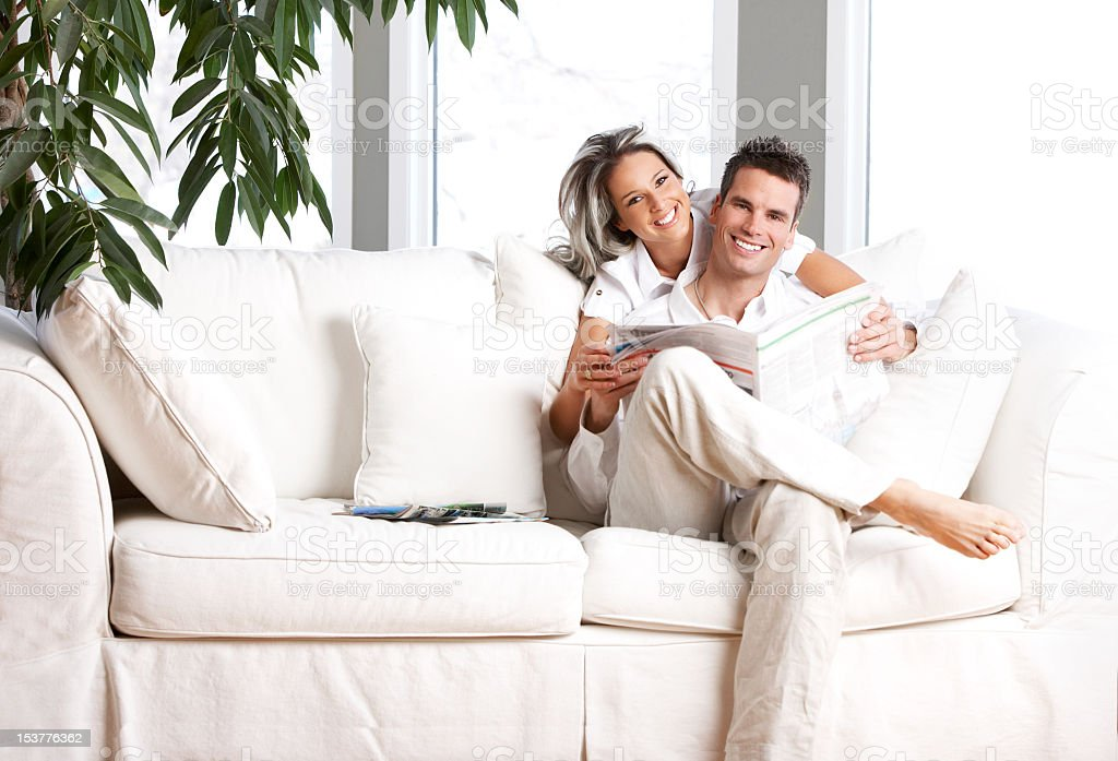 Young couple sitting on white couch reading newspaper royalty-free stock photo