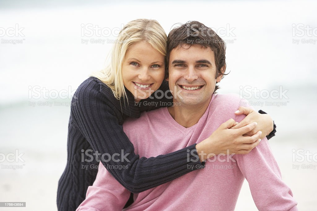 Young Couple Sitting On Winter Beach stock photo