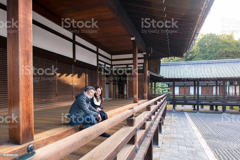 Young couple sitting on wooden deck of Tofukuji temple, Kyoto stock photo