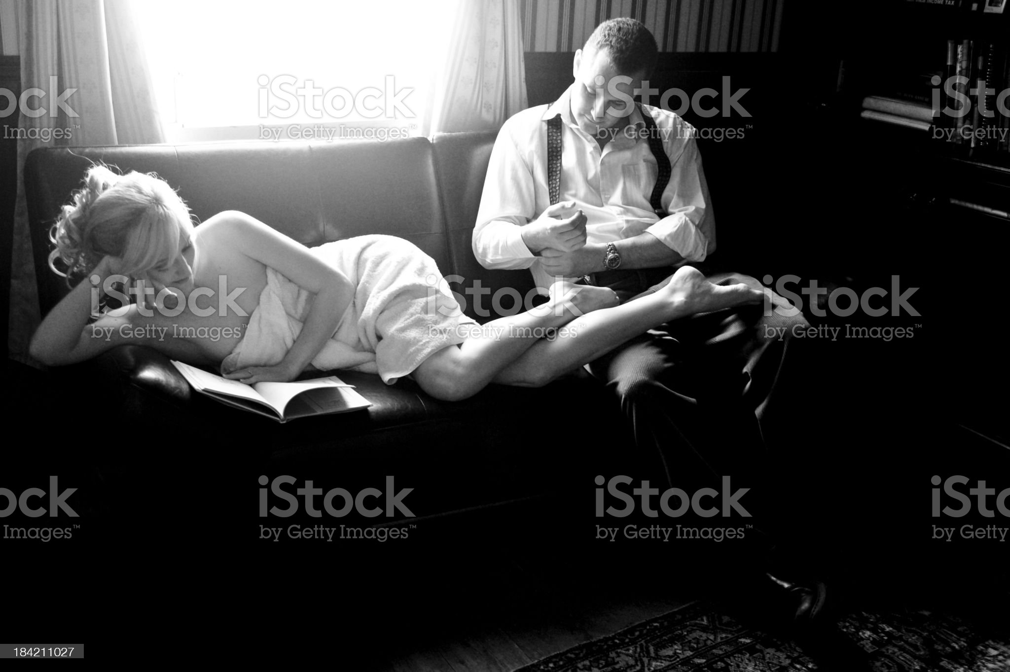 Young couple sitting relaxed on couch inside home royalty-free stock photo