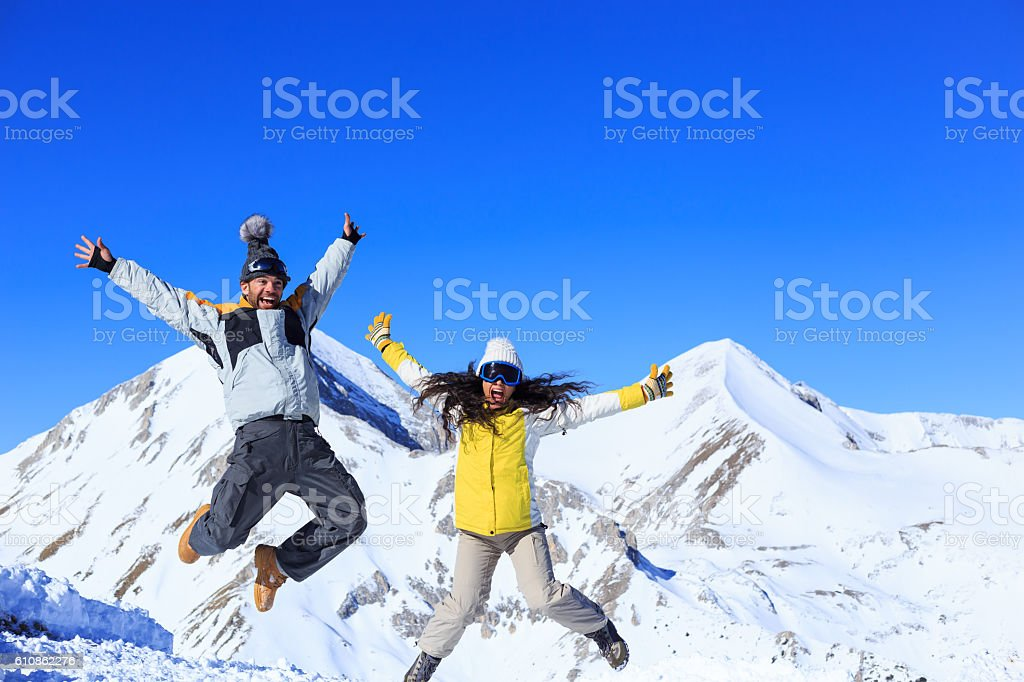 Young couple skiers having fun and jumping in the air stock photo