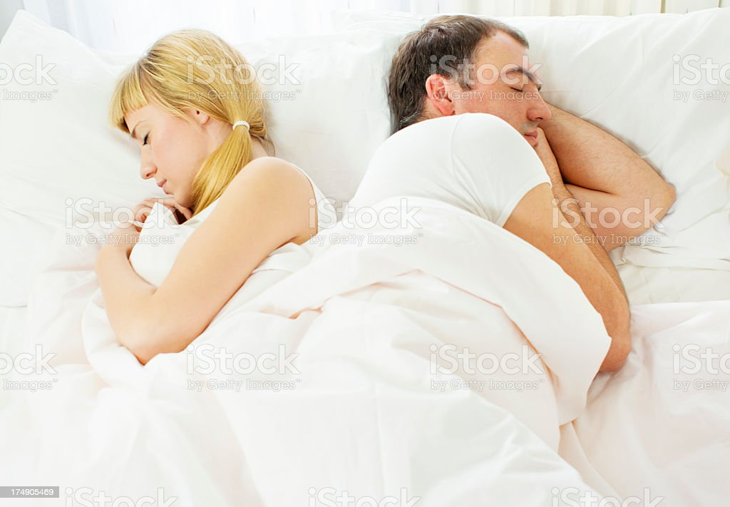 Young Couple Sleeping Back to Back. stock photo
