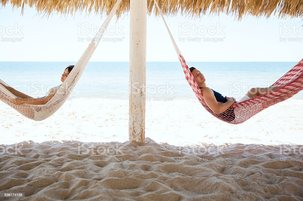 Young couple sleeping in hammocks at the beach stock photo