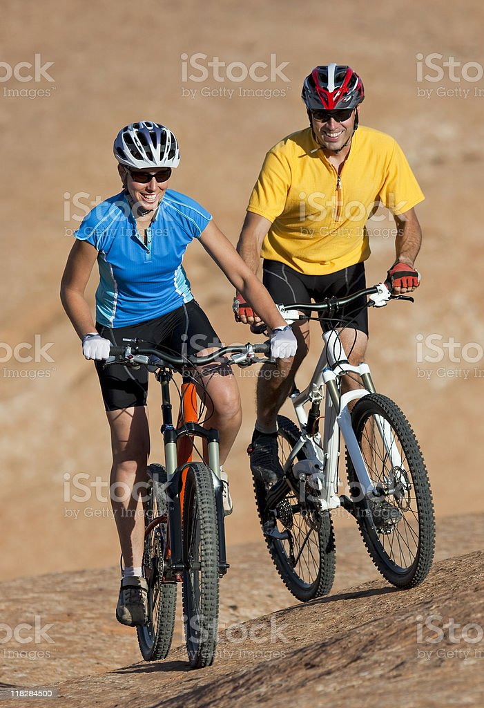Young Couple Smiling And Enjoying Mountain Bike Ride royalty-free stock photo
