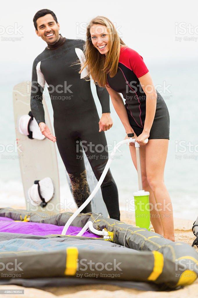 Young couple smiling near kiteboardon stock photo