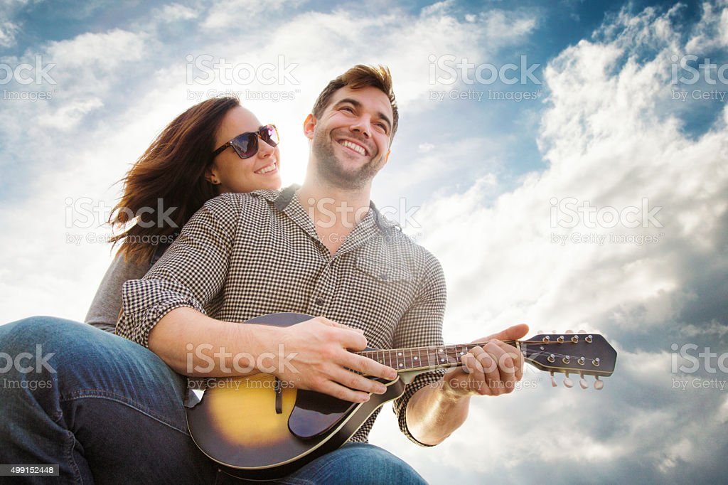 Young couple smiling outoors while man plays country song stock photo