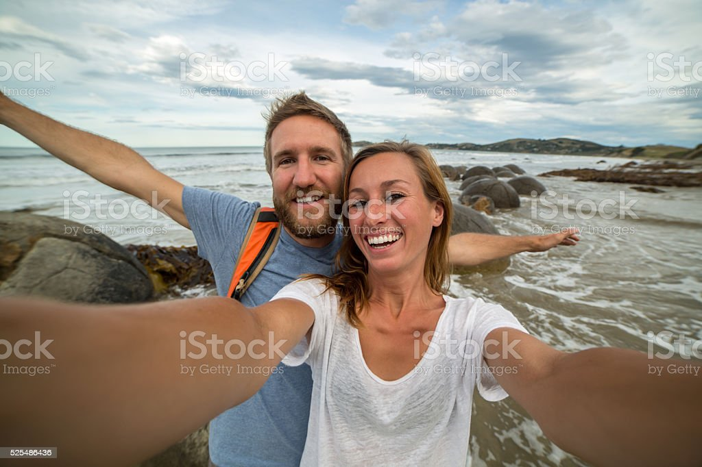 Young couple stand near Moeraki boulders and take selfie portrait stock photo