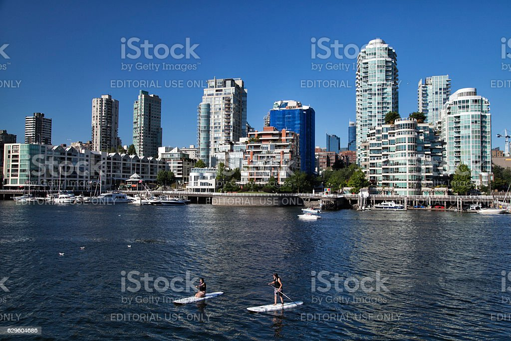 Young couple stand paddling at False Creek, Vancouver stock photo