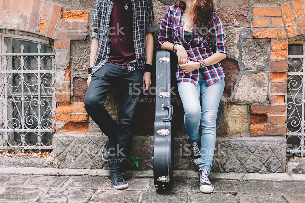 Young couple standing against a wall stock photo
