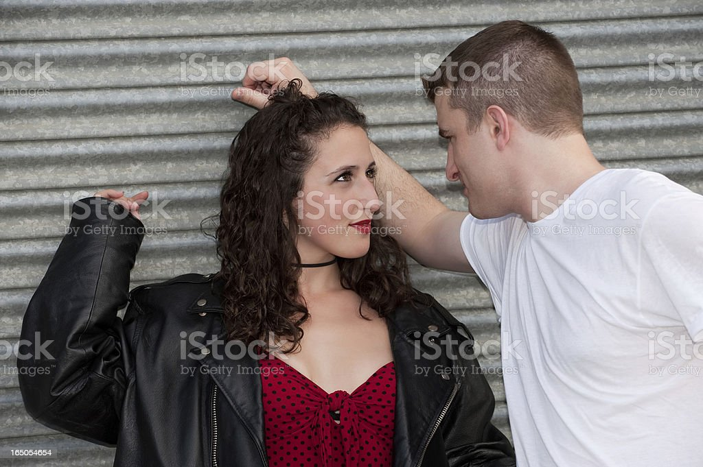 Young Couple Standing Against Corrugated Door Looking At Each Ot stock photo