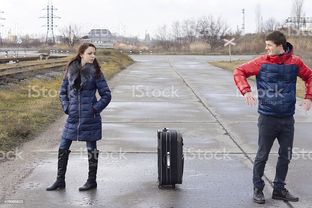 Young couple standing arguing in the road stock photo