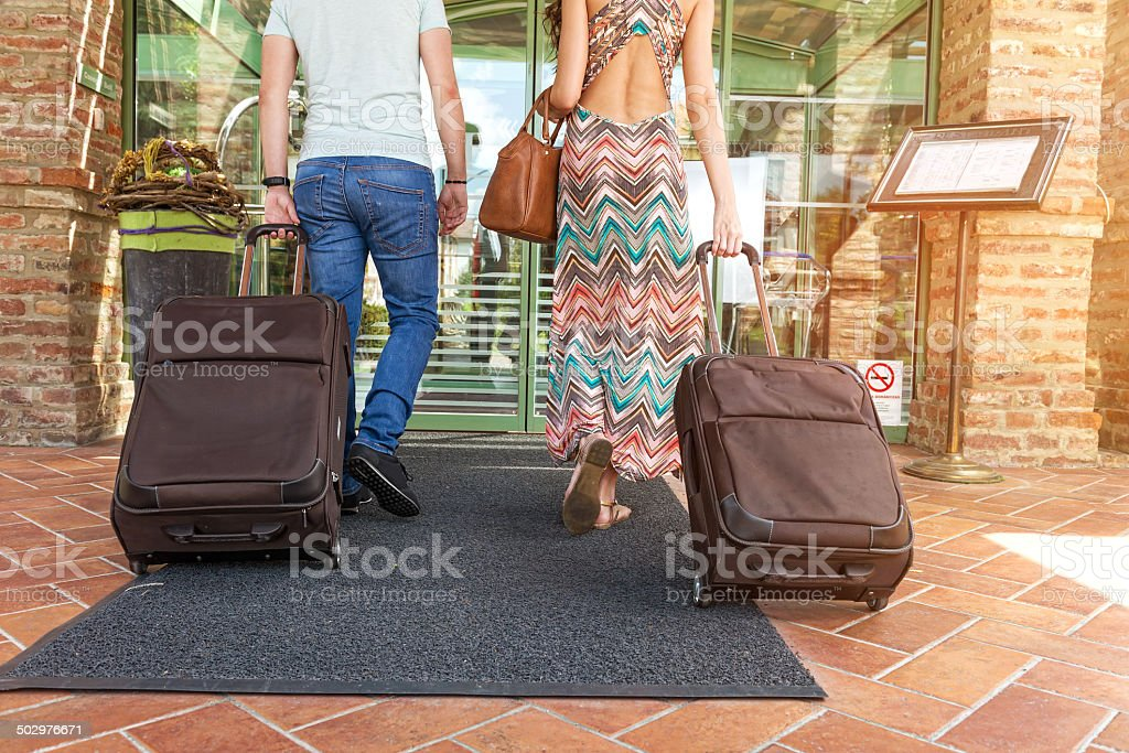 Young couple standing at hotel corridor upon arrival stock photo