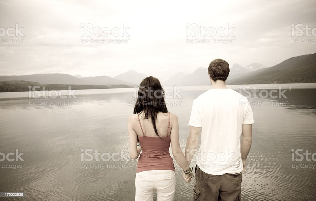 Young couple standing at the edge of a lake royalty-free stock photo